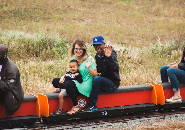 Happy family riding train mom dad son