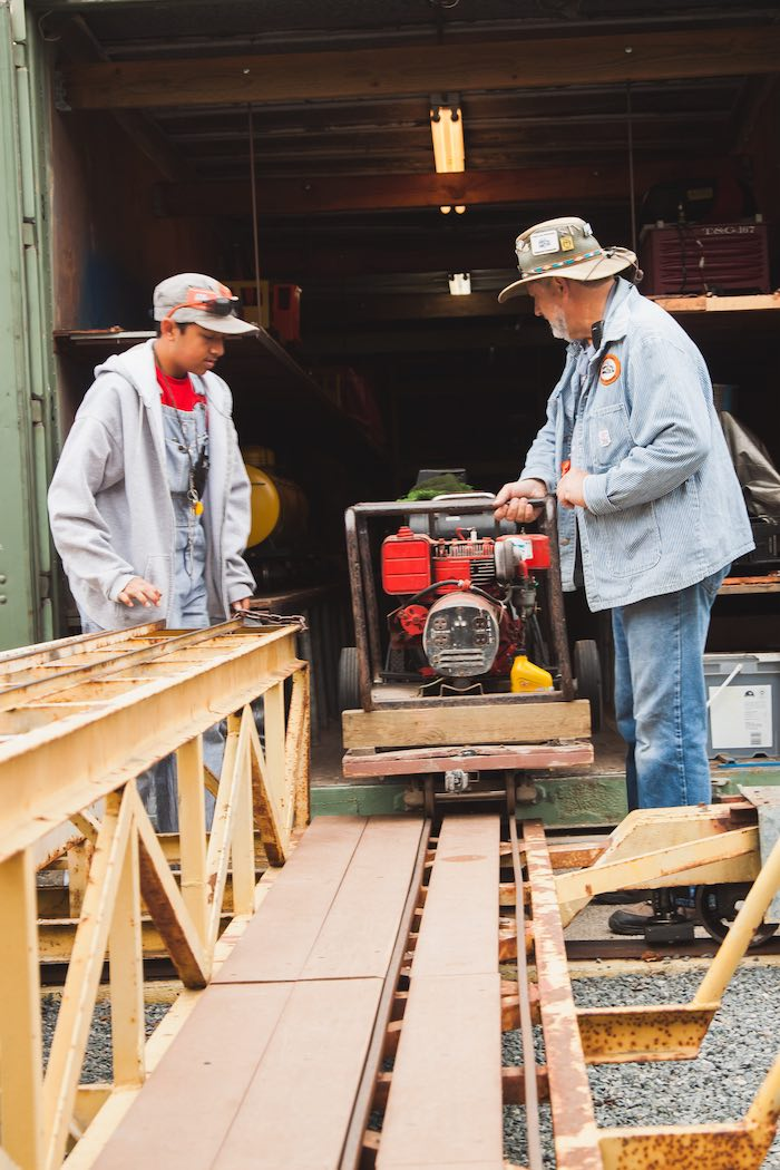 Two men pulling a model train engine onto the tracks in a train yard