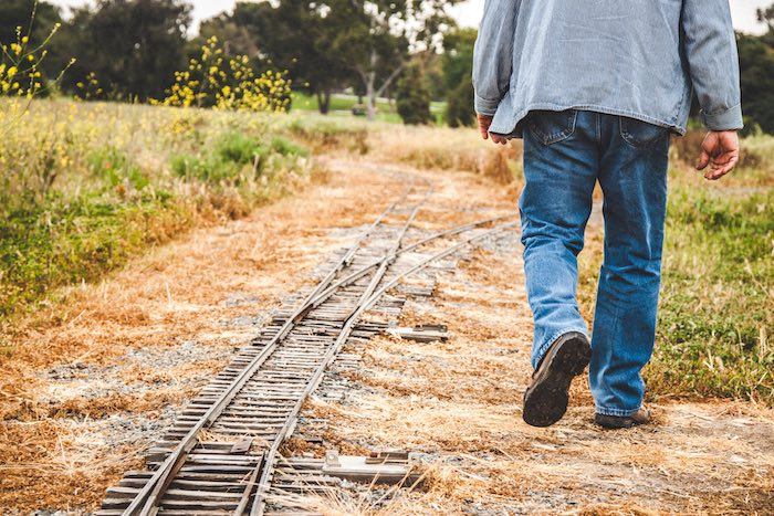 Photo of a man walking along the train tracks